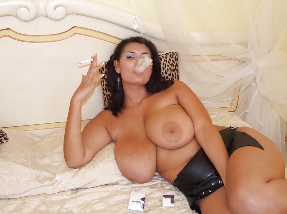 Привлекательная шатенка курит обнажив груди